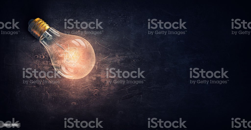Glowing bulb on stone surface . Mixed media stock photo