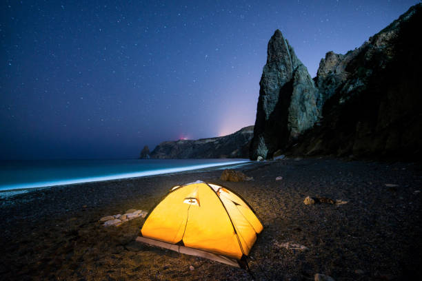 Glowing camping tent on a beautiful sea shore with rocks at night under a starry sky stock photo