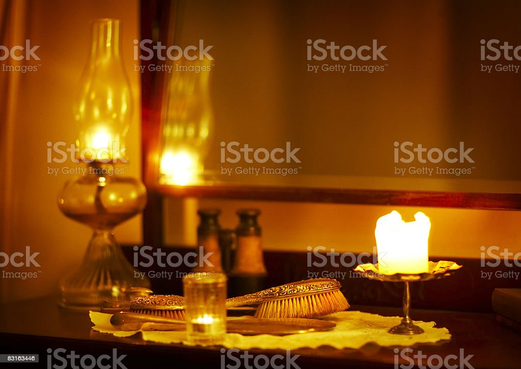 Glowing candles on top of vanity  with antiques royalty free stockfoto