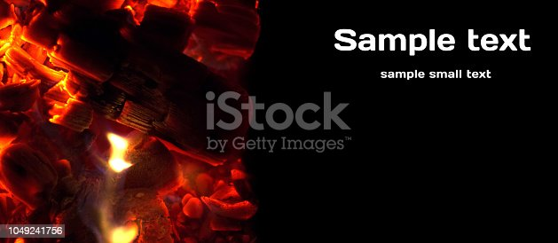 istock Glowing charcoal close-up pieces text banner landscape layout 1049241756