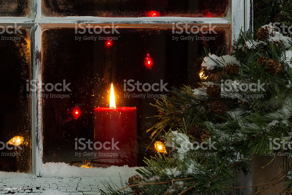 Glowing Christmas candle in frosted home window stock photo