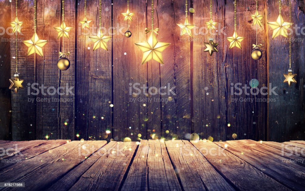 Glowing Christmas Stars Hanging At Rustic Wooden Background stock photo