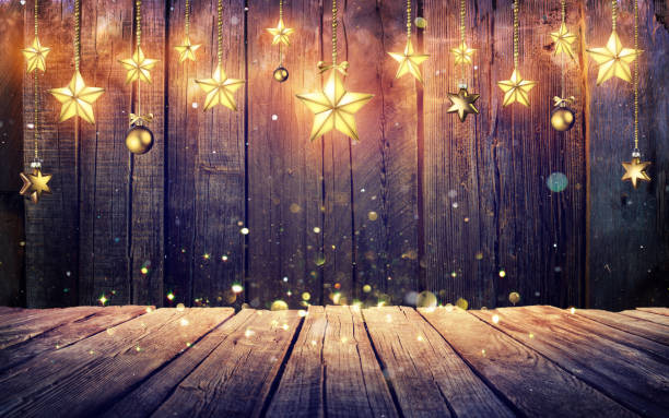 glowing christmas stars hanging at rustic wooden background - vintage ornaments stock photos and pictures