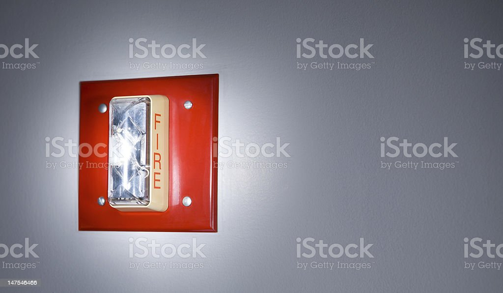 Glowing Closeup of a Red Fire Alarm Unit Indicator stock photo