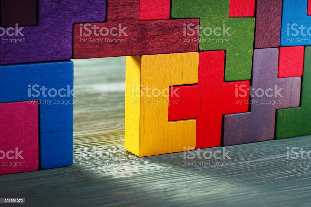 Glowing doorway, colorful wall of wooden puzzles. stock photo