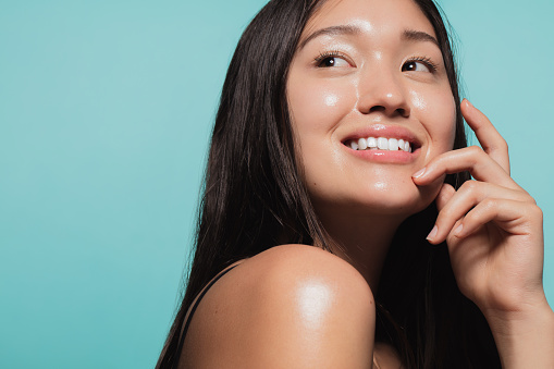 Close up of cute asian girl with glowing skin against blue background. Beautiful face of girl with fresh healthy skin.