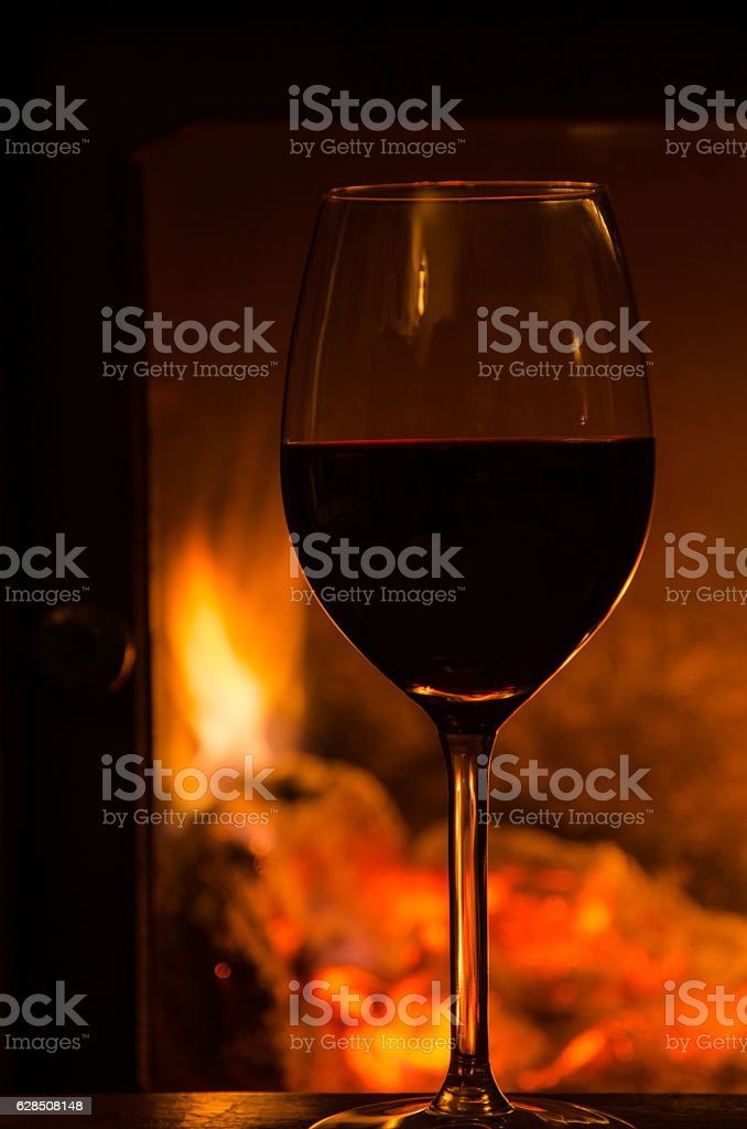 Glowing fire with a glass of red wine stock photo