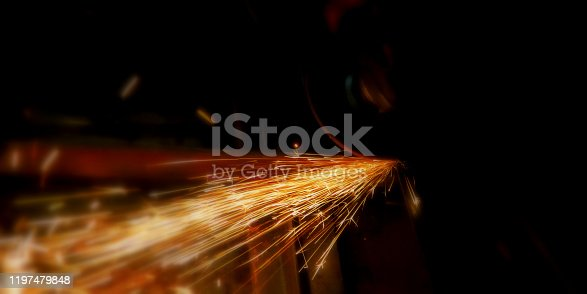 Glowing flow of steel or metal grinding spark particles shine in the dark background.Welder in workshop manufacturing metal construction by cutting to shape using huge orange sparks.Craftsman sawing metal with disk grinder in workshop.Selective focus.