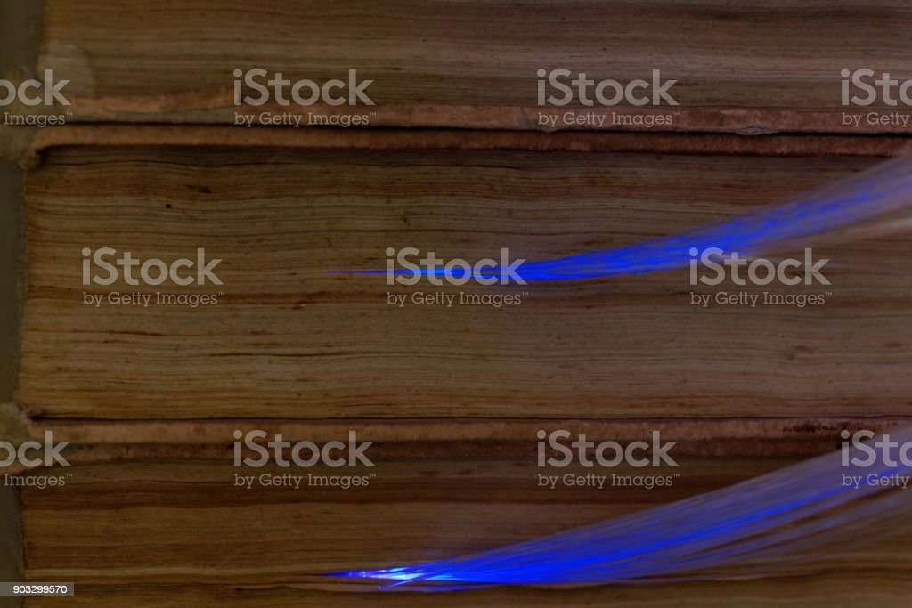 Glowing glass fiber cables connected with old books stock photo