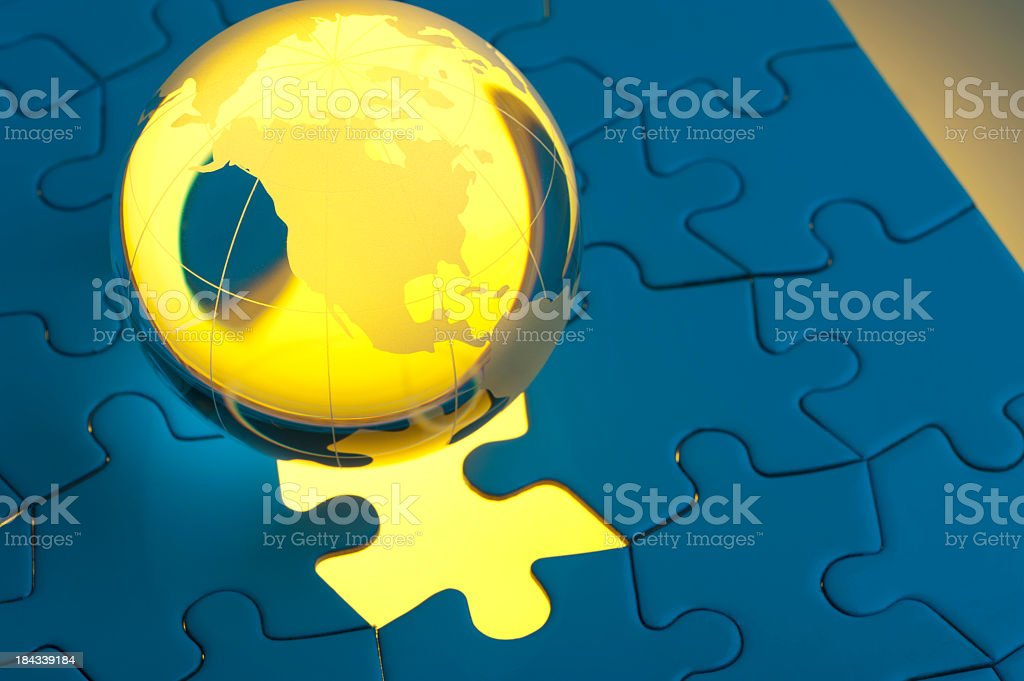 Glowing globe on a blue jigsaw with missing piece royalty-free stock photo
