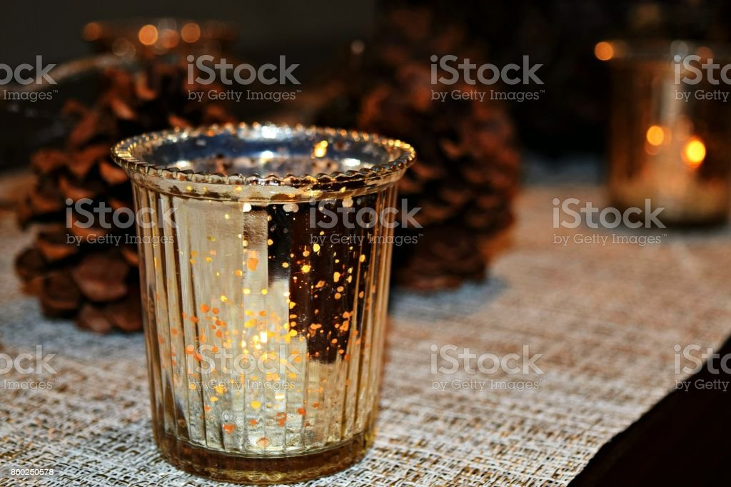 Glowing Gold Candlelight and Pinecone Holiday Centerpiece stock photo