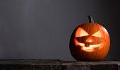 Glowing Halloween pumpkin head jack lantern on gray old wooden background