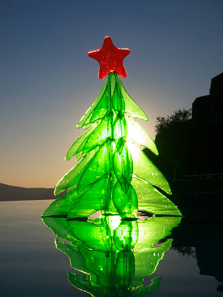 glowing inflatable toy christmas tree floats on reflective pool stock photo