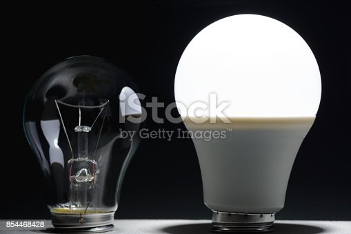 854468792 istock photo Glowing led lamp and incandescent bulb in the dark 854468428