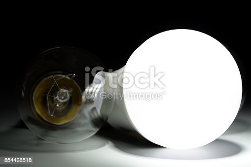 854468792 istock photo Glowing led lamp and incandescent bulb in the dark 854468518