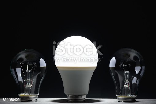 854468792 istock photo Glowing led lamp and incandescent bulbs in the dark 854468402