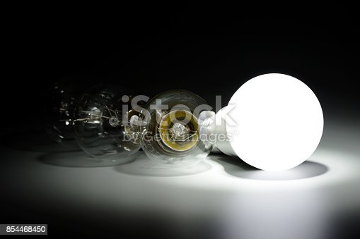 854468792 istock photo Glowing led lamp and incandescent bulbs in the dark 854468450