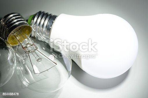 854468792 istock photo Glowing led lamp and incandescent bulbs in the dark 854468478