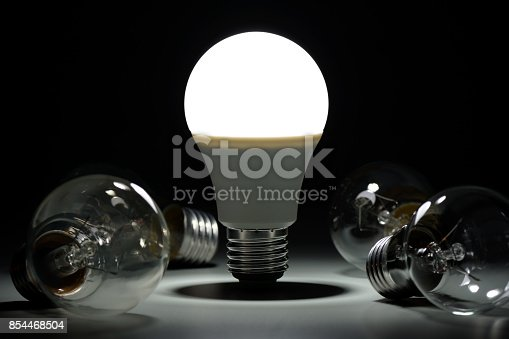 istock Glowing led lamp and incandescent bulbs in the dark 854468504