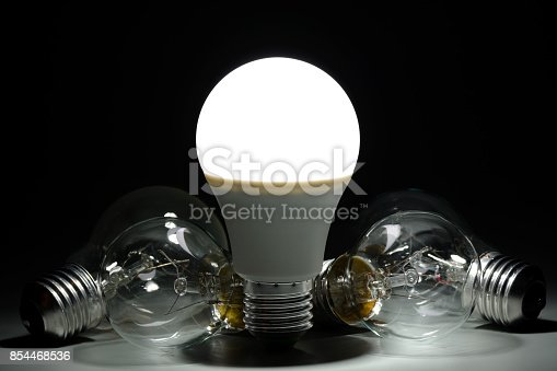 854468792 istock photo Glowing led lamp and incandescent bulbs in the dark 854468536