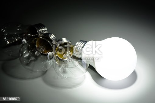 854468792 istock photo Glowing led lamp and incandescent bulbs in the dark 854468572