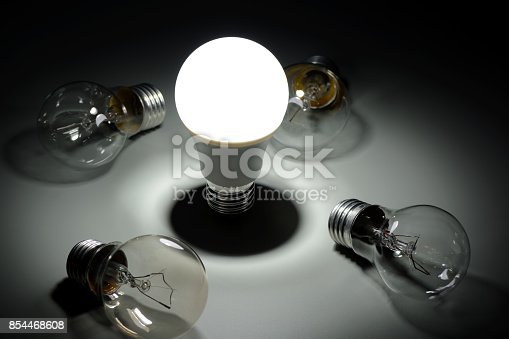 854468792 istock photo Glowing led lamp and incandescent bulbs in the dark 854468608