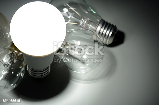 854468792 istock photo Glowing led lamp and incandescent bulbs in the dark 854468618
