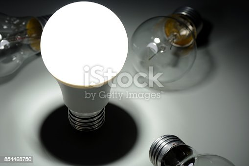 854468792 istock photo Glowing led lamp and incandescent bulbs in the dark 854468750