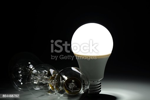 istock Glowing led lamp and incandescent bulbs in the dark 854468752