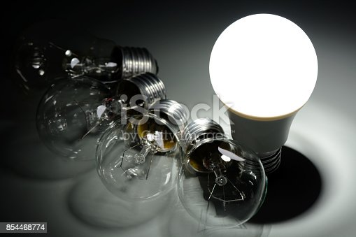 854468792 istock photo Glowing led lamp and incandescent bulbs in the dark 854468774