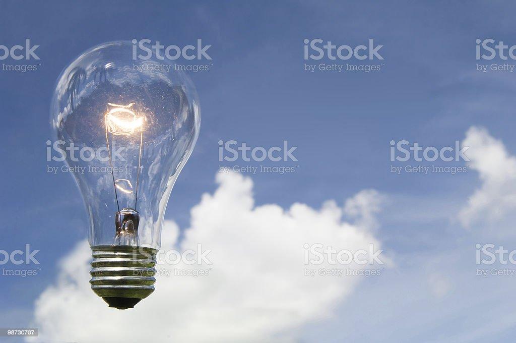 Luminosa lampadina contro il cielo blu con nuvole foto stock royalty-free