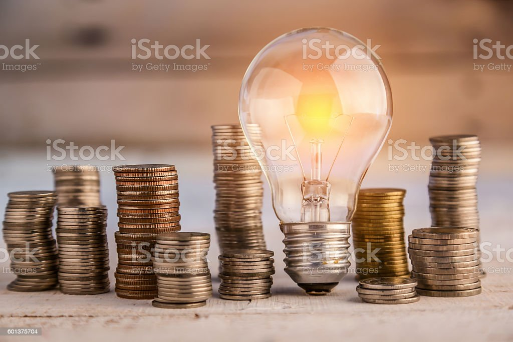 glowing light bulb among many coins stock photo