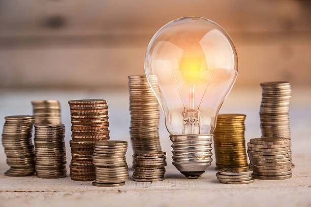 glowing light bulb among many coins - energie sparen stock-fotos und bilder