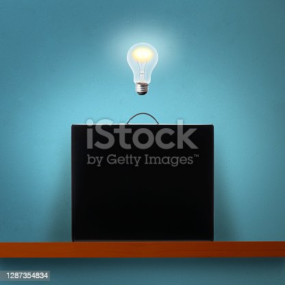 istock Glowing light bulb in mid-air over the black briefcase on a wooden shelf against blue wall 1287354834