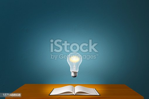 Glowing light bulb in mid-air over the desk with open blank book against blue concrete wall with copy space.