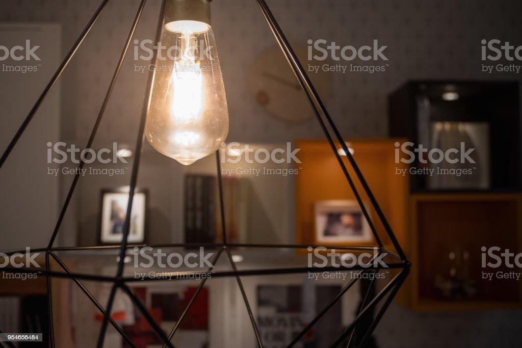 Moderne Lampen 95 : Eine leuchtende glühbirne in moderne lampe mit unscharfen dekoration