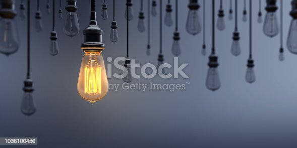 Glowing Light Bulb between the others on dark background. Can be used leadership, innovation and individuality concepts.  (3d render)