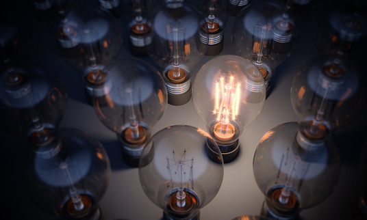 Glowing Light Bulb between the others. Can be used leadership, innovation and individuality concepts.  (3d render)