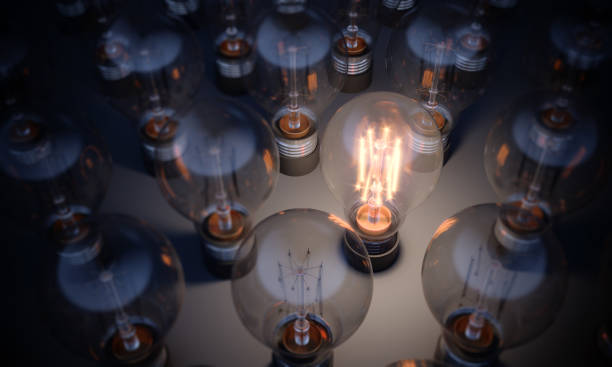 Glowing Light Bulb Standing Out From the Crowd Glowing Light Bulb between the others. Can be used leadership, innovation and individuality concepts.  (3d render) light bulb stock pictures, royalty-free photos & images