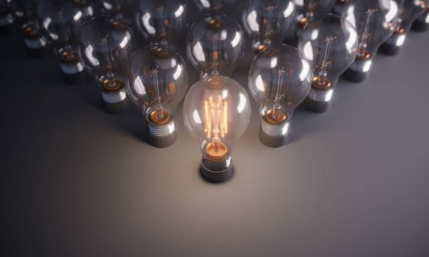 Glowing Light Bulb Standing Out From the Crowd stock photo