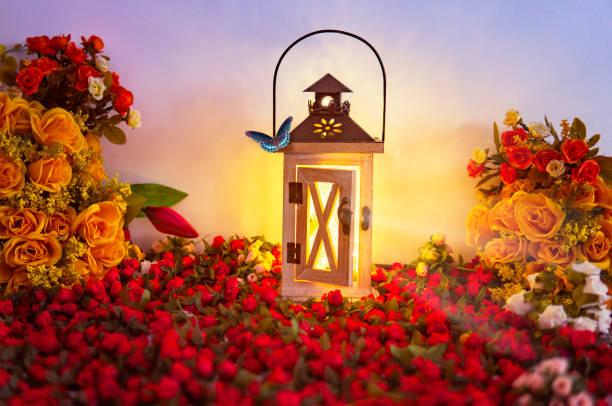 Glowing Light Lantern in Beautiful Spring Floral Arrangement Creative Scene stock photo