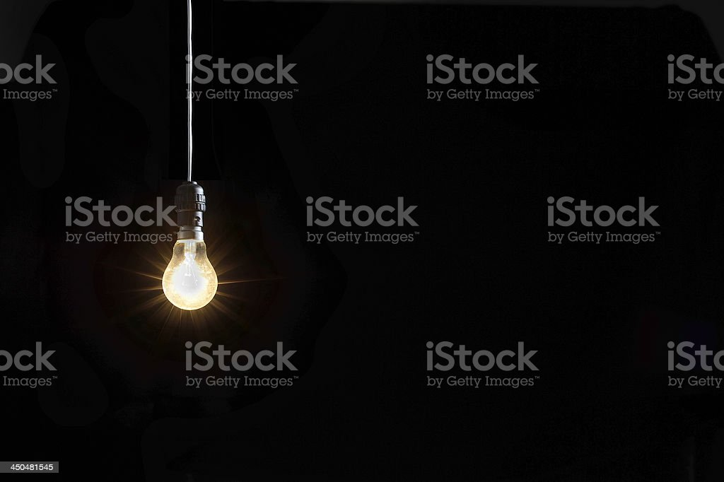 Glowing lightbulb against black background stock photo