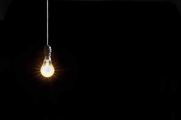 Leuchtende Glühbirne auf schwarzem Hintergrund – Foto