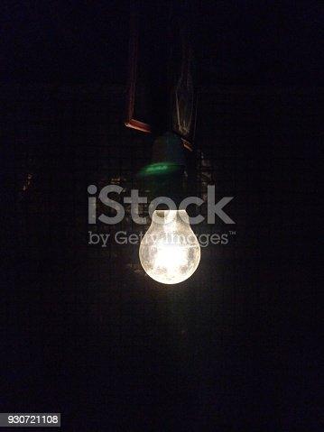 637573406istockphoto Glowing lightbulb in dark 930721108