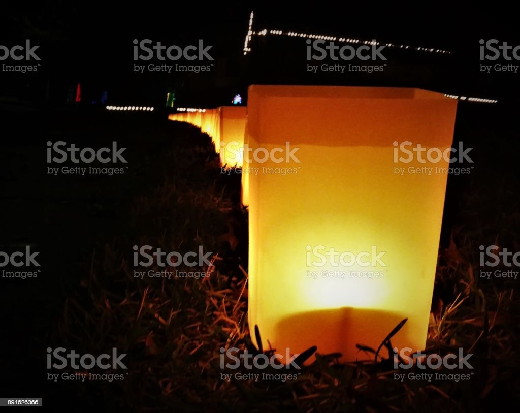 Glowing Luminaria 'Paper Bag' Decorations on a Lawn for Christmas -- Night stock photo