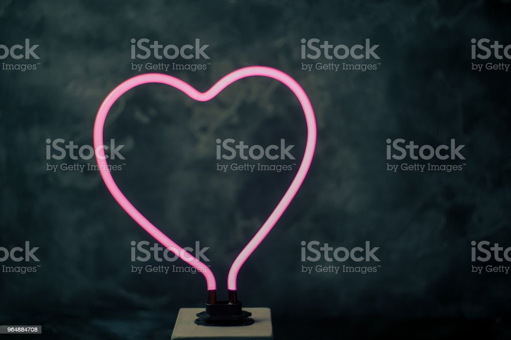 glowing neon heart shape with black textured back royalty-free stock photo