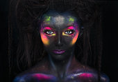 Glowing neon makeup with dramatic look in his eyes. Creative body art on the theme of space and stars.