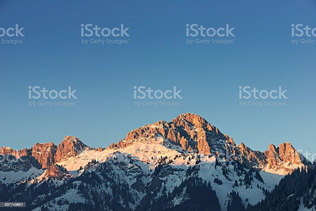 glowing orange mountain peak at sunset in tirol alps stock photo