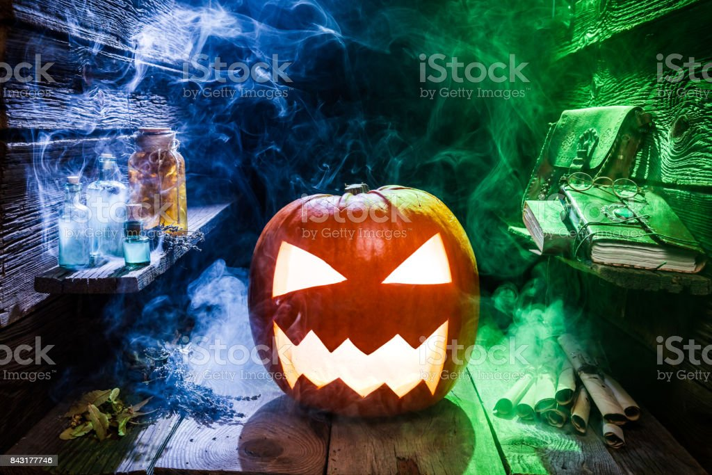 Glowing pumpkin for Halloween in witcher hut with color smoke stock photo
