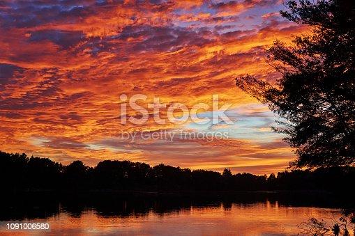 Glowing sky over the forest lake. Mecklenburg-Vorpommern, Germany